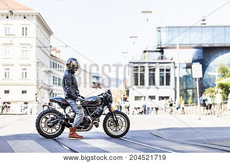 Cool looking motorcycle rider on custom made scrambler style cafe racer in the city