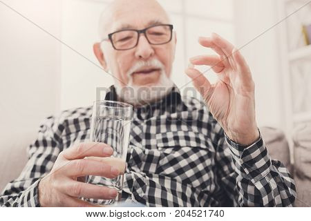 Old man taking pills with water glass. Healthcare, treatment, aging concept