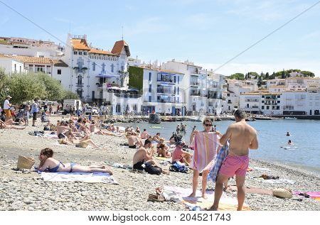 CADAQUES, SPAIN - JULY 27, 2017: People in the beach on a summer day at the beach of Cadaques a town in the province of Girona Catalonia Spain.