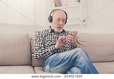 Senior man listening to music on smartphone with headphones, sitting on sofa at home, copy space