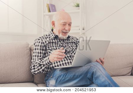 Smiling senior man reading news on laptop. Cheerful excited mature male using portable computer at home