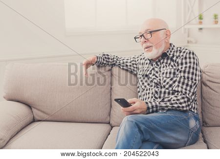Calm senior man watching tv, sitting on couch with remote controller, copy space