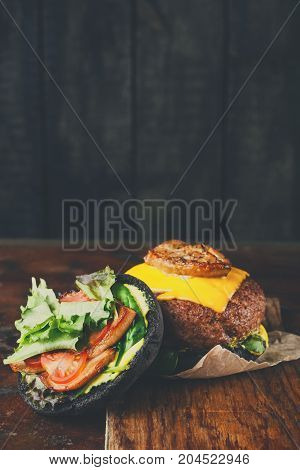 Black bun burger on wooden tray copy space. Open cheeseburger with cutlet and vegetables, fast food concept