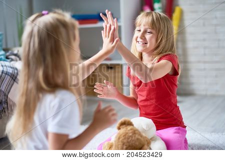 Smiling fair-haired little girls playing pat-a-cake while gathered together at cozy living room, blurred background
