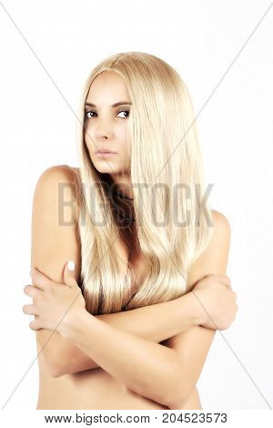 naked girl with long blond hair crossed her arms over her breasts on a white background