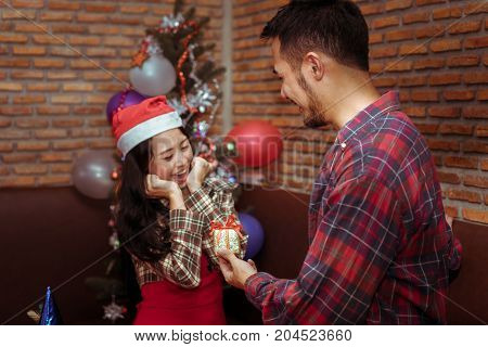 Young man surprise small gift box for girlfriend couple together in x'mas party with santa hat and celebrate lover at home