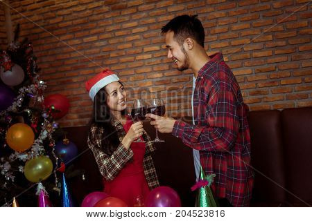 Young man and woman couple together in x'mas party with santa hat and drinking wine celebrate lover at home