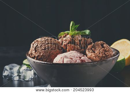 Portion of chocolate and berry ice cream scoops with ice on black background, copy space. Delicious cold sweet dessert
