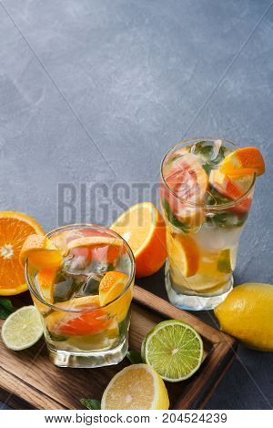 Summer citrus drinks background. Healthy detox water in glasses and fruits variety on wooden board on gray table. Colorful backdrop with oranges, lemon and lime, copy space