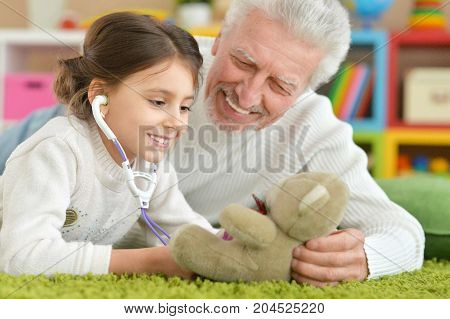 Portrait of a grandfather playing with granddaughter in room