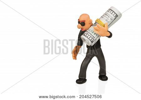 Bald plasticine man with glasses carries on his shoulder a bundle of dollars isolated on a white background