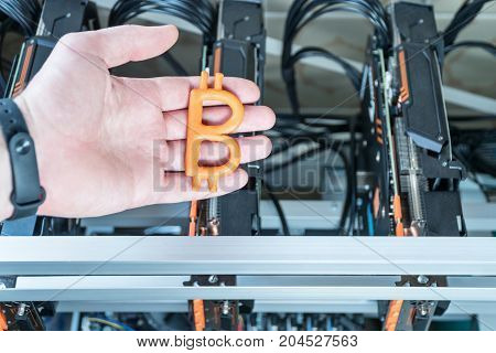 Man hand holds a plasticine bitcoin against the backdrop of a mining farm from video cards