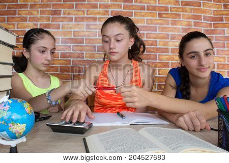 Three girls sitting at desk at home doing homework. Portrait of two pretty girls high school student studying. Thoughts education creativity concept