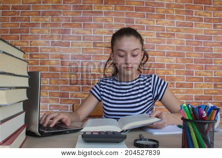 Young Girl and writing information she has found in a large book into her notebook. Thoughts education creativity concept