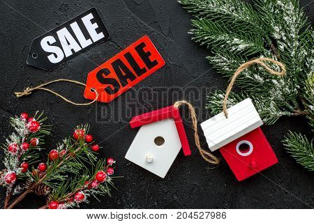 Christmas sale. Sale labels near spruce branch and xmas toys on black background top view.