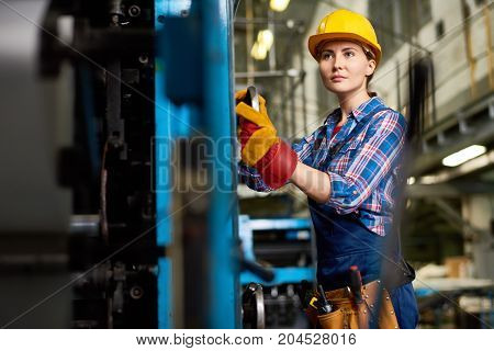 Confident young engineer wearing overall and checked shirt looking away while carrying out inspection at manufacturing plant, blurred background