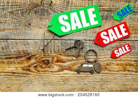 Colored sale labels and car keys on wooden background top view.