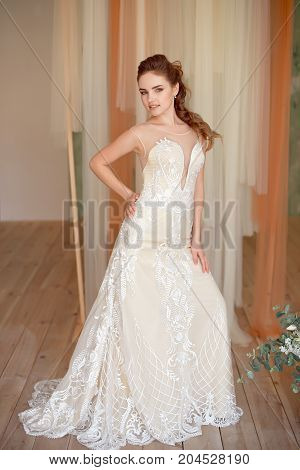 Full-length portrait of Beautiful luxurious female model with medium brown hair in a long white wedding dress in the room. Bridal clothes concept. Stylish wedding dress.