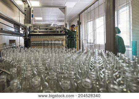Brest, Belarus - July 05, 2017: Brest Distillery Unloading glass bottles with an automatic machine.