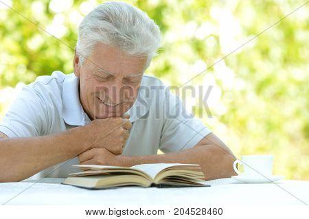 Portrait of senior man reading interesting book outdoors