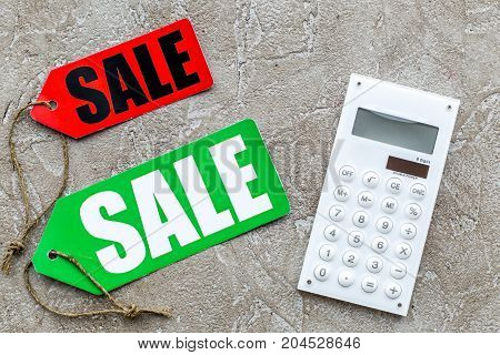 Count the benefits from the sale. Word sale on label near calculator on light stone background top view.