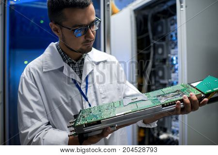 Portrait of young scientist wearing lab coat holding blade server while working with supercomputer in blue room