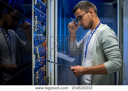 Side view  portrait of young man standing by server cabinet while working with supercomputer in data center and holding clipboard