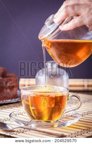 Pouring tea from a transparent glass teapot into a clear glass cup on a saucer