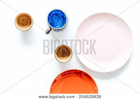Crockery. Empty cups and plates on white background top view.