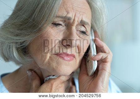 Portrait of upset senior woman talking on the phone