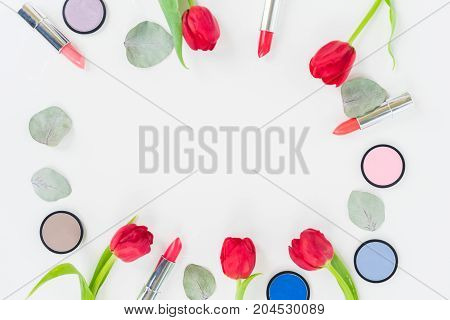 Colorful make up and tulips flat lay frame with copy space