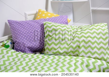 Beautiful and bright pillows lie on the child's bed in the room