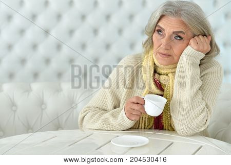 happy Senior woman  at table with tea cup