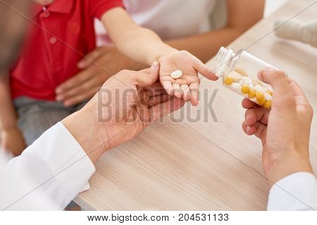 Close-up shot of unrecognizable pediatrician giving vitamins to little patient sitting on laps of his mother
