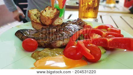 Grilled pork neck steak with vegetables and beer