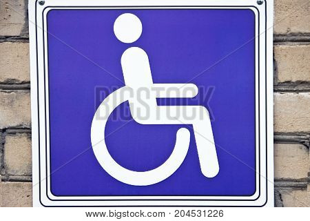 Sign of a man in a wheelchair on a brick wall