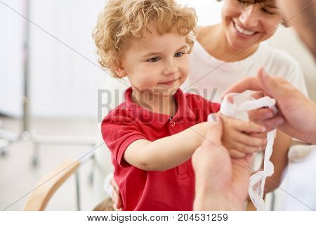 Unrecognizable doctor putting bandage on injured finger of cute little boy, his pretty mother looking at him with toothy smile