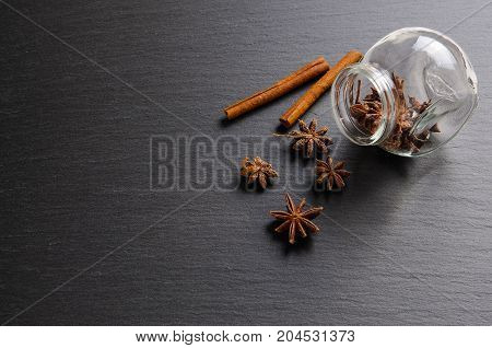 Brown ingredients: anise star, cinnamon sticks and glass jar