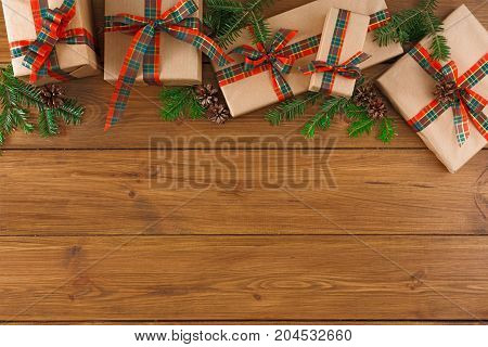 Creative presents in craft and grey paper decorated for any holiday concept. Gift boxes, fir tree branch, top view with copy space on rustic table background.