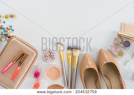 Top view of female fashion accessories - handbag pursue, cosmetics, brushes, shoes