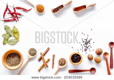 Kitchen table with spices and dry herbs on white kitchen desk background top view mock up