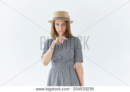 Picture of attractive worried serious young European woman in dress and hat keeping index finger at her lips saying Shh Hush asking to keep silent. Secrecy silence and conspiracy concept