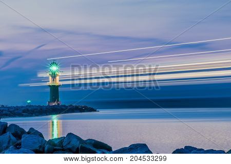 night view of lighthouse of Warnemuende on the Baltic Sea at the harbor with light stripes from ship , Germany Rostock