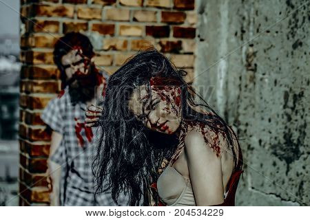 Halloween girl vampire with red blood. Blur man or war soldier with wounds. Holiday celebration concept. Zombie couple in torn clothes standing on brick wall. Woman with bloody brunette hair.