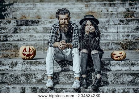 Halloween hipster couple sitting on grey stairs. Girl in felt hat hiding face with hands. Bearded man with pumpkin. Woman with jack o lantern. Halloween holiday celebration concept.