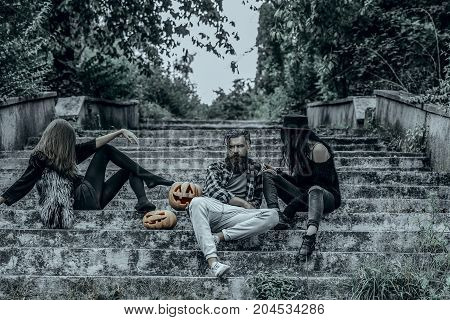 Halloween holiday celebration concept. Halloween people and jack o lanterns. Friends on stony stairs. Women with pumpkin heads. Bearded man sitting with girls.