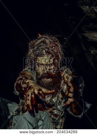 Halloween vampire hipster with red blood and wounds. War soldier sitting in torn clothes. Halloween holiday and horror concept. Man with bloody hands on dark background. Zombie with scary face.