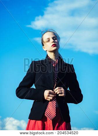 Girl posing on blue sky. Model in red tie and jacket. Fashion and accessories concept. Summer vacation and wanderlust. Woman relaxing on nature on sunny day.