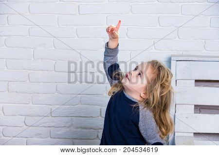 Baby boy in room. Toddler pointing index finger up. Child with long blond hair on white brick wall. Playing and having fun. Happy childhood concept.