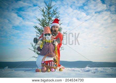 Man Posing With Snowy Sculpture On Cloudy Sky